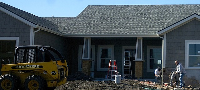 Workers add shingle siding to a new home being built in the Signal Ridge subdivision. It was one of 10 homes to be started or built this year in Baldwin City thanks to a grant awarded the community meant to stimulate housing starts.