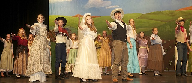 "The cast of the Baldwin High School fall musical sing the praises of ""Oklahoma!"" during a Tuesday dress rehearsal. The students will perform the musical at 7 p.m. Friday and Saturday in the BJHS Performing Arts Center."
