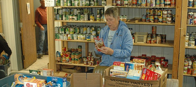 Pat Matthews, BLAS member, checks expiration dates as she sorts through food donations collected by USD 458 students at the BLAS food pantry. Having just received large donations of food and toiletries for the pantry, the assistance organization is now seeking donations for its Christmas Adopt-a-Family program.