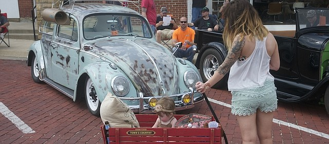 A young mother stops to look at a vintage VW bug at the Baldwin City Chamber of Commerce car show in June. The show was one of many events that drew visitors to the community, and was one of many events that kept the chamber busy after it added Hank Booth its first-ever executive director. Later in the year, Jennette Blackmar state as office manager at its new office location in the Lumberyard Arts Center.