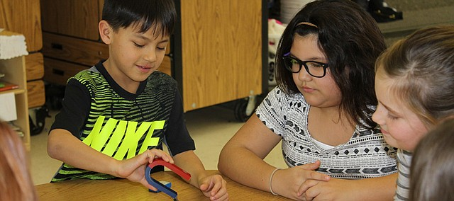 Jonah Volavongsa (left) uses a magnet to test the magnetism of various items as Sayge McCoy and Lily Bendau look on Friday during a Science Enrichment lesson offered by the Ray Marsh Elementary PTA.