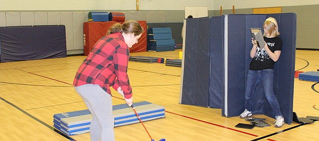 Alexis Kahler (right), sixth grade student at Bluejacket-Flint Elementary, uses an iPad to film classmate Anne Miesner as she prepars a chip shot in physical education. P.E. classes are continuing to incorporate more academic skills and at BJF, even a little bit of technology.