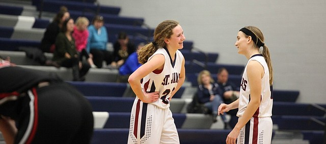 St. James sophomore Mary Goetz and senior Ali Burke share a laugh during the middle of the Lady Thunder's 24-1 run against Metro on Wednesday.