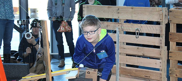 Oscar Ohly leans over as he explains the intended trajectory of Broken Arrow's Rube Goldberg machine during the Rube Goldberg competition Saturday at the Museum at Prairiefire.