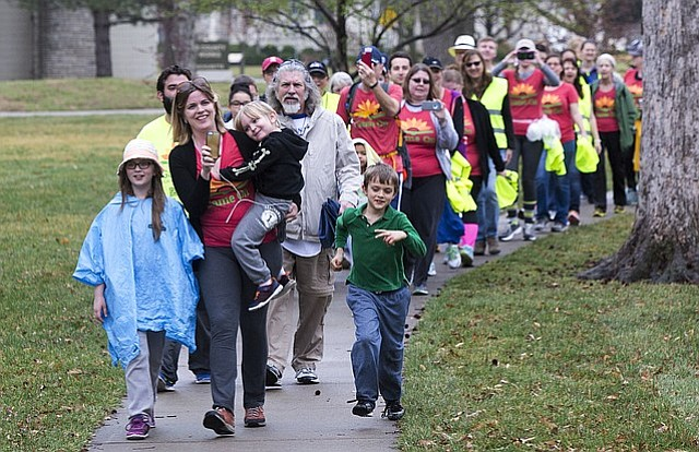 Leading marcher Heather Ousley holds her son Joshua, 4, as daughter Elliannah, 10, and son Samuel, 8, head in to Lawrence's South Park as some 200 parents and teachers welcomed walkers from the Game on for Kansas Schools March to Topeka on Saturday.