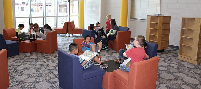 Kindergarteners read in the flexible seating area of the library Wednesday in Shawanoe Elementary's new building. Students had their first day of class in the new school Tuesday.