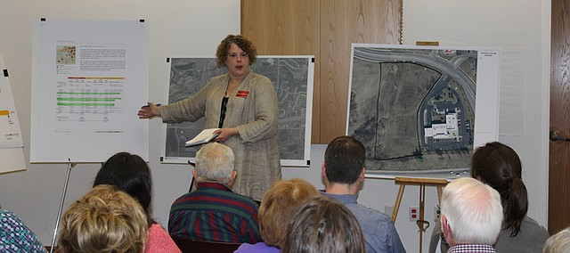 Tricia Suellentrop, deputy county librarian, discusses the history of the Johnson County Library's planning for the Monticello branch at Tuesday's meeting, referring to satellite maps of the site for the new branch and the library's 2015 Comprehensive Plan, which lists construction of the Monticello branch as the top priority.