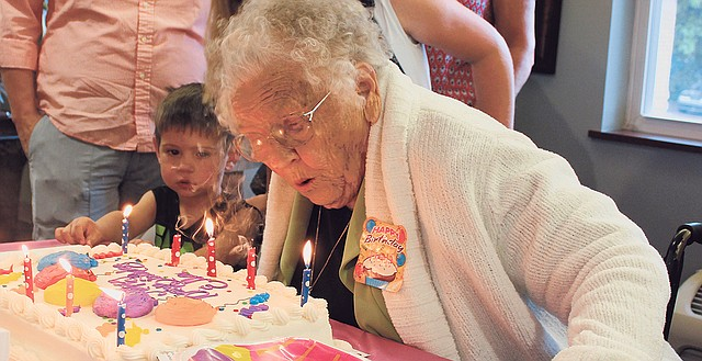 With a number of her family members present, Ella Terbovich begins blowing out the candles on her birthday cake Monday, the day she turned 101 years old.