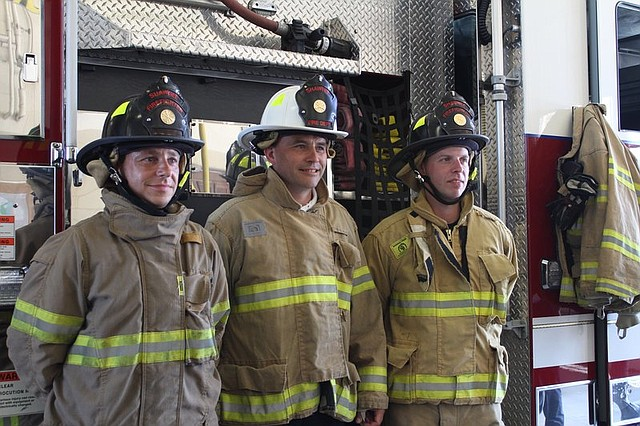 Firemen Lars Peter Zander, Kai Hellstroem, and Rene Siebeo, of Erfurt, Germany, pose for photos at the John B. Glaser fire station in Shawnee.