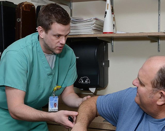 Shown above is KU Med Dermatologist Ryan Fischer, MD, helping a patient at a recent Masonic screening event.