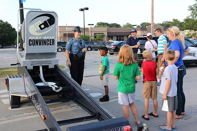 Candice Breshears, a technical trooper for the Kansas Highway Patrol, showcased a seatbelt convincer, which simulates car crashes at a low speed, at National Night Out.