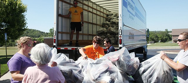 Members of Sacred Heart Catholic Church in Tonganoxie load shoes into a truck. The church's religious studies program will receive money for the shoes it collected.
