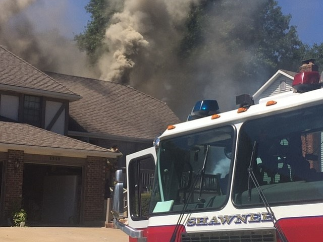 Firefighters battle a house fire in the 6900 block of Widmer Road on Monday afternoon.