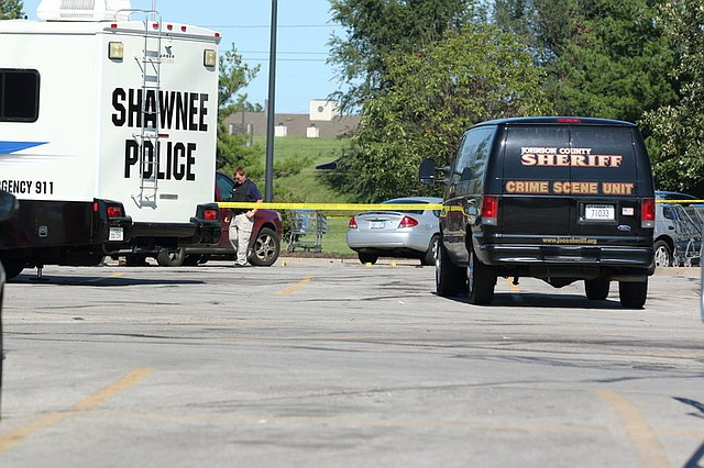 Evidence markers are strewn out across the corner of the Walmart parking lot as Shawnee Police and the Johnson County Sheriff's Office Crime Lab investigate Sunday afternoon's shooting.