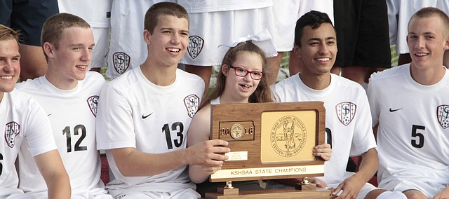 St. James senior soccer players Brady Manning (left) and Luis Alvarado (right) hold the Class 5A state championship plaque with Thunder cheerleader Bella DeBrevi. DeBrevi, who was born with Down syndrome, is considered by the Thunder as their biggest fan. Her brother, Alessandro DeBrevi, wore No. 21 in honor of her because the third copy of the 21st chromosome is where the genetic disorder is found.