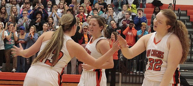 Shawnee Mission Northwest's Sarah Petersen, right, and Emmalee Rose, middle, high-five teammate Haley Nunnink, left, after the Cougars' 36-31 win Tuesday over Mill Valley.