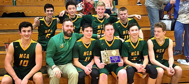The Maranatha Christian Academy boys basketball team gathers for a photo after winning the third-place game of the McLouth tournament on Saturday. The Eagles defeated Cair Paravel, 82-71.