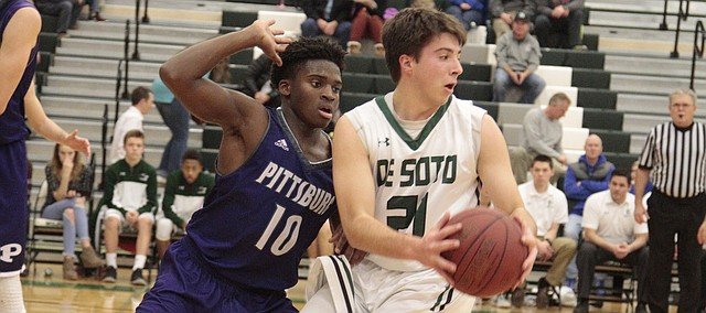 De Soto senior Alex Wilcox gets closely guarded by Pittsburg's Elijah Harris in the second half of the Wildcats' 75-39 loss to the Dragons, Friday.