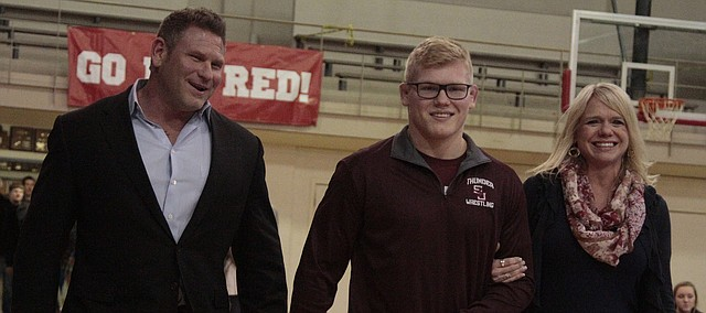 St. James Academy senior Clay Lautt (middle) walks with his father Jon Lautt (left) and mother Sheri Lautt (right) during a senior night ceremony before the Thunder's duals against St. Thomas Aquinas and Bishop Miege.
