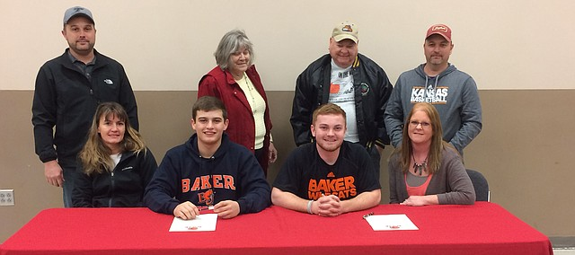 Tonganoxie High's Devan Graham, middle left, and Jordan Brown wear their Baker University garb for National Signing Day this past Wednesday, Feb. 1. The teammates and friends signed letters of intent to play football at BU, which went 14-1 this past fall and was national runner-up in NAIA. pictured with Graham and Brown are their parents, Erica and Travis Graham and Jackie and Mike Brown. Standing behind Jordan are his grandparents Bob and Sharon Curtin.