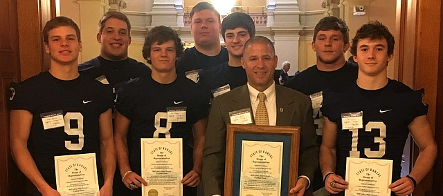 Mill Valley coach Joel Applebee and eight of his players were recognized for the Jaguars' back-to-back Class 5A state championships on Wednesday at the Kansas State Capitol Building during Wednesday's House of Representatives meeting. Front row (left to right): Junior Brody Flaming, senior Ben Hartman, head coach Joel Applebee and senior Joel Donn. Second row: Seniors DJ Graviette, Jack Bauer, Blaine Boudreaux. Third row: senior Keegan Zars.