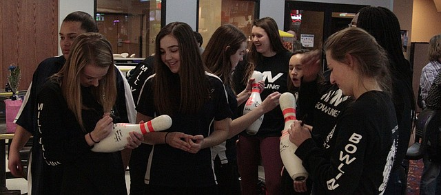 Mill Valley seniors Raya Lehan (far left) and Lauren Tracht (far right) sign each other's senior night bowling pin gift after the Jaguars' triangular Monday at Park Lanes. Lehan won the tournament with a series of 535, and Tracht rolled a strike to round out the Jaguars' first-place finish.