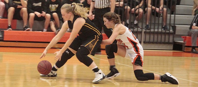 Shawnee Mission Northwest junior Jordann Nachbar (right) dives for a loose ball against Shawnee Mission West's Kayla Henrie in the Cougars' 43-32 loss on Friday against the Vikings.