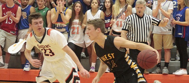 Shawnee Mission West's Zach Witters looks to drive by SM Northwest junior C.C. Ghilardi in the first half of the Vikings' 75-60 win over the Cougars on Friday.