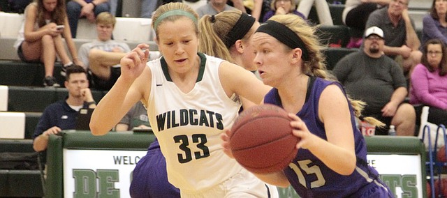 Louisburg senior Madisen Simpson dribbles by De Soto senior Madison Plake in the first half of DHS' 34-31 home loss on Tuesday.