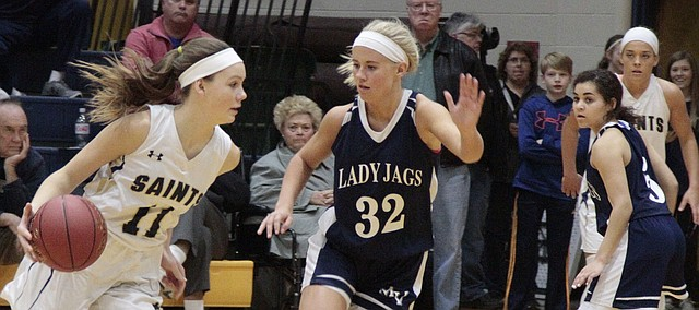Mill Valley senior Courtney Carlson slides over to cut off the lane against St. Thomas Aquinas sophomore Blythe Pearson in the Jaguars' 46-34 loss to the Saints in the Class 5A sub-state championship game on Friday.