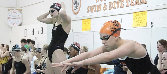 Shawnee Mission North junior Joely Merriman (left) and SM Northwest senior Hailey Brull (right) stand on the diving blocks before the 400-yard freestyle relay in the SMSD swim and dive meet on Saturday at SM Northwest.