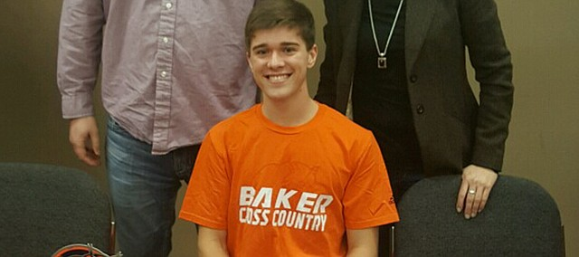 Tonganoxie High's Drew Cook signs in February to run cross country and track at Baker University during a ceremony at the Chieftain Room on the Tonganoxie High School campus. Standing with Drew are his parents, Andy and Marcia Cook.