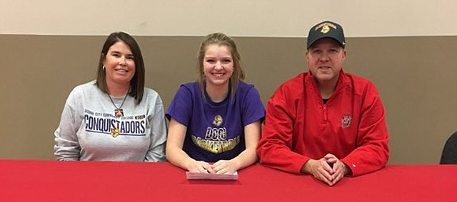 Taylor Lee signs a National Letter of Intent earlier this year to play basketball at Dodge City Community College. Lee, who graduated in May from Tonganoxie High, was a three-sport athlete at THS who holds a handful of school records in girls basketball. Also at the signing were her parents, Brandi Lee, at left, and Scott Lee, at right.