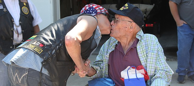 Didi Lincoln, Leavenworth, greets Dave Underwood with a kiss Saturday morning. American Legion Riders on 30 bikes from across northeast Kansas visited Underwood to show their appreciation for his service in World War II.