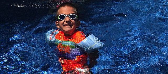 Bo Macan, 7, swims in his new pool on June 16. Swimming is one of the few activities that Macan — who has rheumatoid arthritis, diabetes, epilepsy and growth hormone deficiency — can do without pain. Several helping hands came together to support Macan with the pool — including McCarthy Mortenson NBAF A Joint Venture, Pools By York, Starr Homes and many other organizations and individuals.