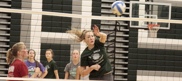 De Soto junior Hannah Wilson follows through on a spike during a drill at the Wildcats' volleyball camp on Friday.