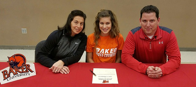 Emily Chambers signs a letter of intent earlier this year to compete in cross country and track at Baker University in Baldwin City. Joining her at the signing were her parents, Jenny and Jason Chambers.
