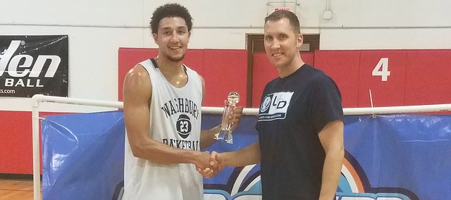 Shawnee Mission Northwest alumnus and Washburn senior Brady Skeens, left, accepts the Dream League Most Valuable Player trophy.