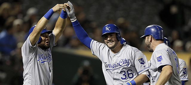 Kansas City Royals' Cam Gallagher (36) is congratulated by Melky Cabrera, left, after hitting a grand slam off Oakland Athletics' Jharel Cotton in the sixth inning of a baseball game Monday, Aug. 14, 2017, in Oakland, Calif.