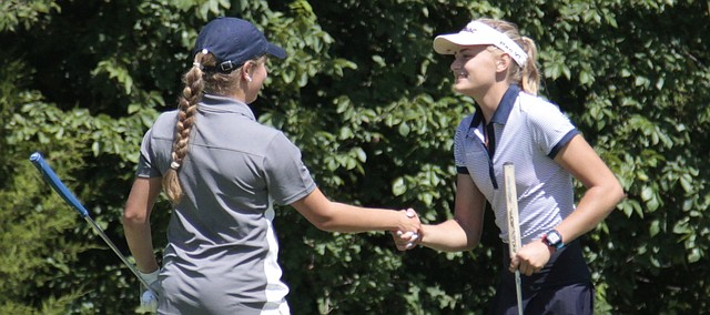 Mill Valley senior Bella Hadden, right, shakes hands with St. James sophomore Allison Comer after finishing the 18th hole of the Cat Classic on Wednesday at Shawnee Golf & Country Club. Hadden won the tournament after shooting a round of 2-over-par 74.