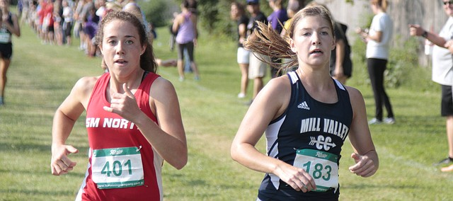 Shawnee Mission North junior Katie Kasunic, left, and Mill Valley senior Britton Nelson, right, close in on the finish line at the Greg Wilson Classic on Saturday at Johnson County Community College.