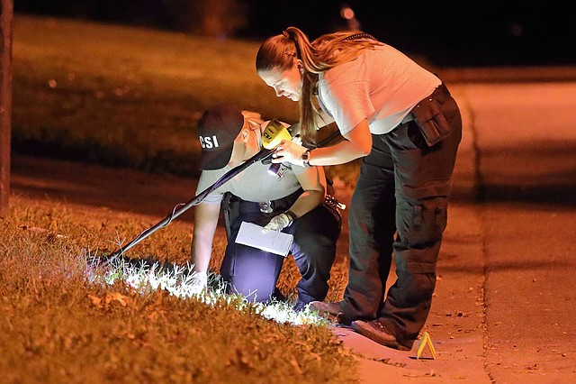 Johnson County Sheriff's Office Crime Scene Investigators searched the front yard of the home where the disturbance occurred with a metal detector.
