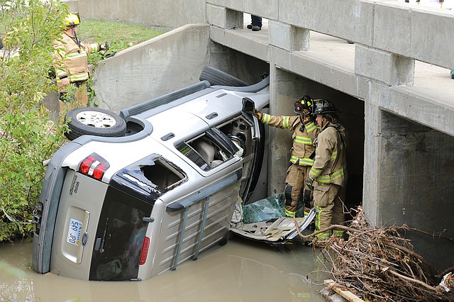 Shawnee Firefighters on the scene of a fatal crash in the 10400 block of Shawnee Mission Parkway on Saturday morning. Firefighters used the 'Jaws of Life' to remove a section of the vehicle's roof to better access the man inside.