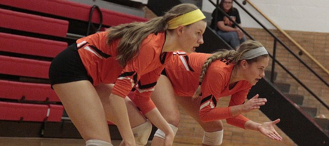 Shawnee Mission Northwest freshman Taylor McCarthy, left, and junior Hannah Black, right, prepare for a point in the third set of the Cougars' loss to Lawrence High in the championship match of the Class 6A sub-state volleyball tournament on Saturday at LHS.