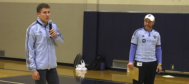 Sporting Kansas City defender Matt Besler, left, speaks to Trailridge Middle School students during an assembly on Dec. 12 which helped honor Trailridge physical education Larry Benson, right, as a Blue KC Sporting Samaritan.