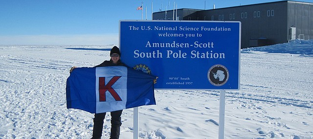 Emily Arnold poses with a University of Kansas flag during a research trip last month in Antarctica. Arnold, an assistant professor at the University of Kansas, is a rural Tonganoxie resident.