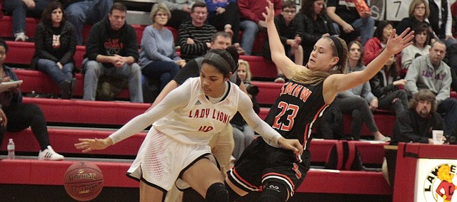 Shawnee Mission Northwest junior Hannah Black stays in front of Lawrence High senior E'lease Stafford in the second half of the Cougars' 51-45 loss to the Lions on Tuesday.