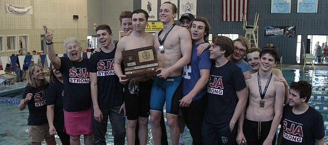 The St. James boys swim and dive team stands on the awards podium with the third-place plaque after the Class 5-1A state meet on Saturday at Capitol Federal Natatorium in Topeka.