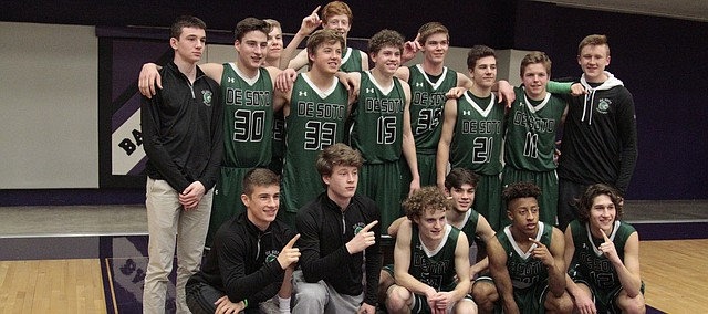 The De Soto boys basketball team gathers for a photo after its 61-52 win over Baldwin on Friday, which clinched the Frontier League title outright for the Wildcats.