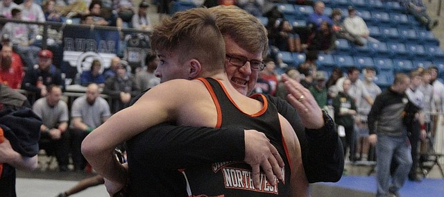 Shawnee Mission Northwest wrestling coach Howard Newcomb hugs senior Jerad Habben at the Class 6A state tournament on Saturday at Hartman Arena in Park City.